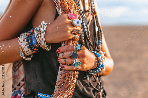 Платно close up of young boho style woman hands with lots of accessories