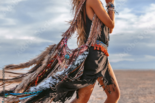 Платно close up of young boho style woman on the beach at sunset