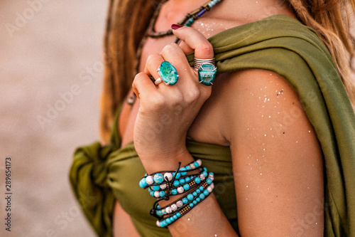 close up of beautiful young stylish woman on the beach at sunset