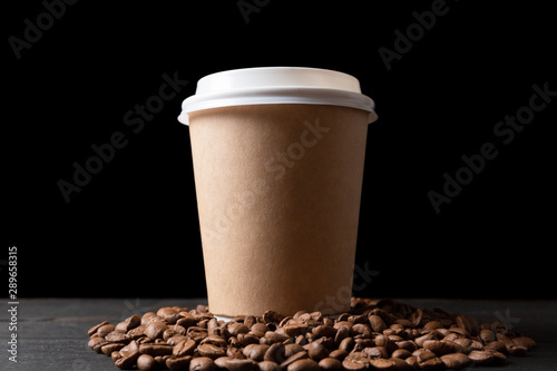 Paper cup of coffee and coffee beans on dark wooden table. Good quality coffee