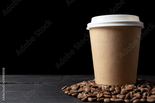 Tuinposter Cafe Paper cup of coffee and coffee beans on dark wooden table. Good quality coffee