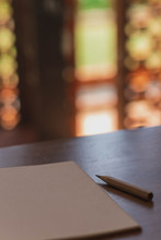 Notebooks And Pencil On Wooden Table With Beautiful Blurred Bokeh Background