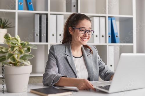 Fotomural  Cheerful intern browsing laptop in office