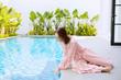 Caucasian woman touching water near the pool