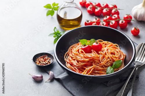 Fotografie, Obraz Pasta, spaghetti with tomato sauce in black bowl on grey background