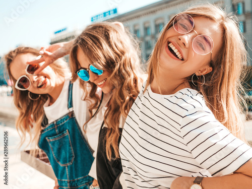 Portrait of three young beautiful smiling hipster girls in trendy summer clothes. Sexy carefree women posing on the street background.Positive models having fun in sunglasses.Hugging