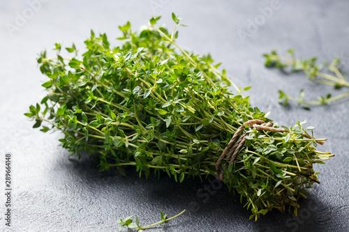 Obraz na plátně Fresh thyme bunch on slate background. Close up.
