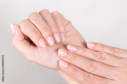 Printed kitchen splashbacks Manicure Closeup top view of beautiful natural pastel manicure at white hands of woman. Horizontal color photography.