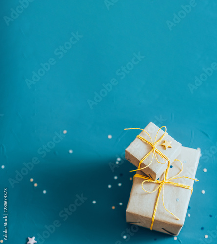 Holiday surprise. Top view of two beige paper gift boxes and round glitter on blur teal blue background. Copy space