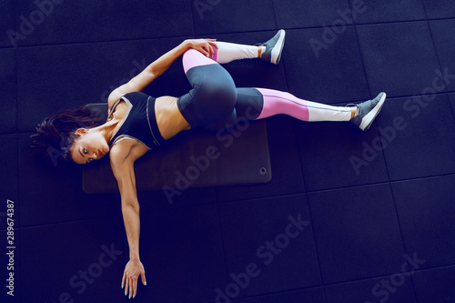 Pinturas sobre lienzo  Top view of muscular brunette in sportswear lying on the mat in gym and doing stretching exercise