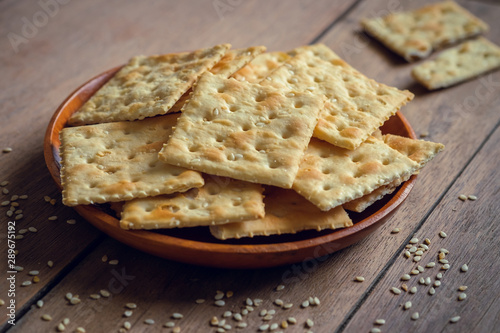 Foto op Canvas Brood Crispy crackers with sesame on wooden plate