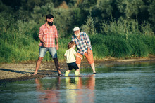 Grandfather , Son And Grandson Throw A Stone And Having Fun On River. Family Generation: Future Dream And People Concept. Male Multi Generation Family.