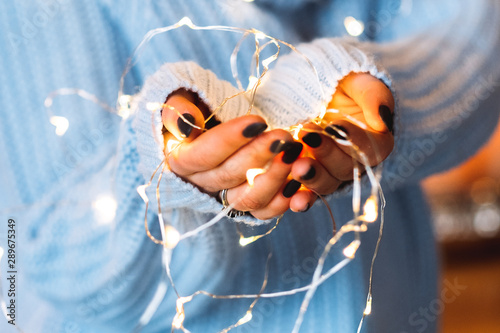 Festive mood. Winter holiday interior decoration. Closeup of white fairy lights in woman hands.