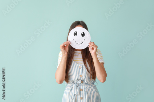 Fotomural  Woman hiding face behind sheet of paper with drawn emoticon on color background