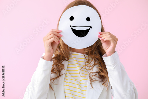 Fotomural  Woman hiding face behind  emoticon on color background
