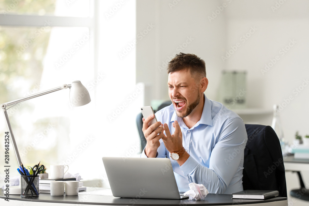 Fototapety, obrazy: Stressed man talking by mobile phone at table in office