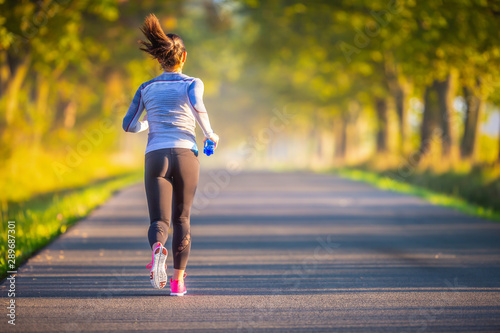 Runner woman in autumn park tree alley training in sports thermal underwear