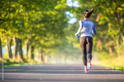 Foto  Runner woman in autumn park tree alley training in sports thermal underwear