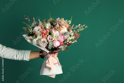 Canvas Print Man holding beautiful flower bouquet on green background, closeup view