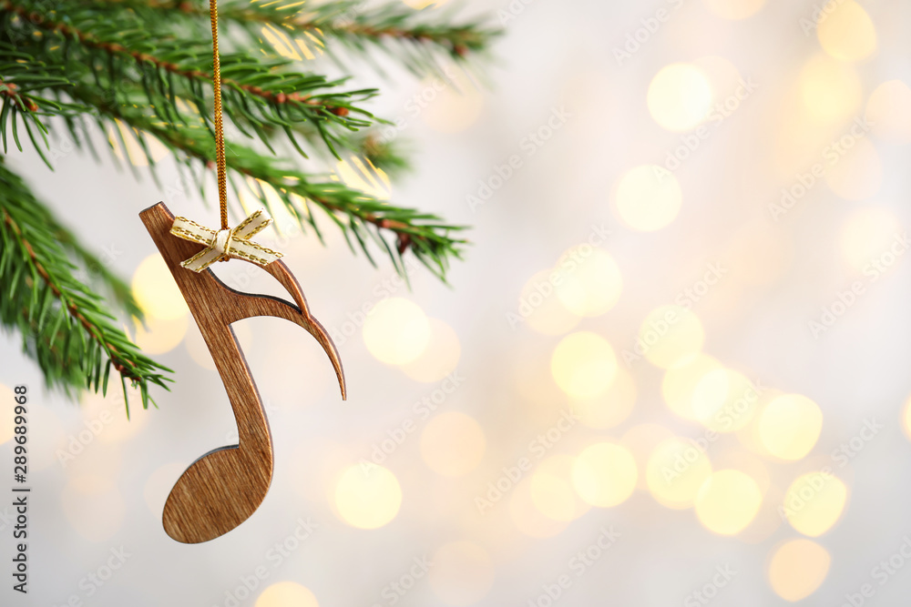 Fototapeta Fir tree branch with wooden note against blurred lights, space for text. Christmas music