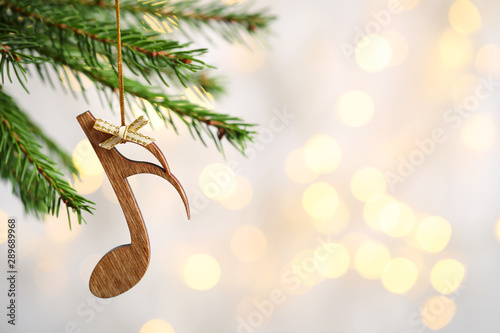 Fir tree branch with wooden note against blurred lights, space for text. Christmas music - 289689968