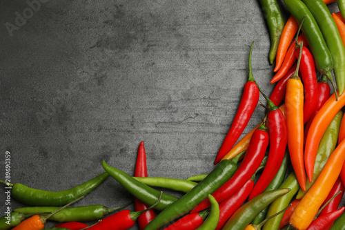 Fototapety, obrazy: Different ripe chili peppers grey table, flat lay. Space for text
