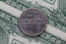 Symmetric Composition Of US Dollar Bills And A Quarter Of North Carolina.