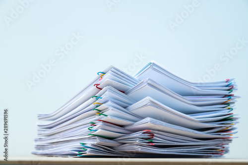 Fotografía Stack of document paper with colorful paperclip place on wooden table with copy space