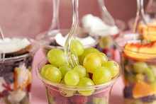 Fresh Tasty Fruit Salad In Plastic Cups On Pink Background, Closeup