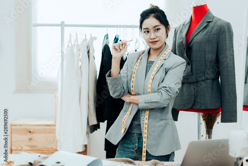 Fotografie, Tablou  Asian young women fashion designer  working on her designer in the showroom,  Lifestyle Stylish tailor taking measurements on mannequin in studio