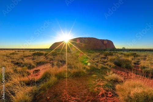 Dramatic sunbeams behind the huge Ayers Rock at down monolith Canvas Print