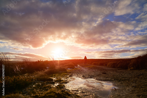 Foto auf AluDibond Lachs A close up of ice filled puddles on a dirt track with a distant hiker at sunset near Edmundbyers and Blanchland in County Durham.