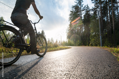 Photo sur Toile Velo A woman rides a bike on a bicycle path in the rain on a summer evening in the sunshine next to a pine forest. Healthy lifestyle concept.