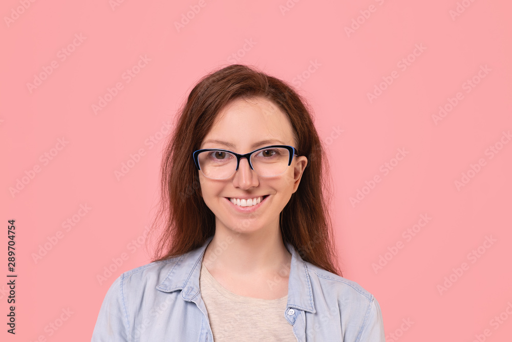 Fototapeta Close-up portrait of a smiling pretty student girl in glasses smiling on a pink background. Happy girl advertises stationery. Advertising space