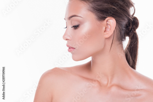 Obraz na plátně  Side view of a beautiful young well-groomed woman with clean radiant skin of her face and body posing on a white background