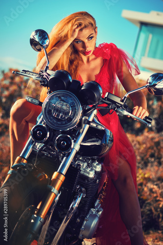 Gorgeous woman wearing red fluffy dress sitting on motorcycle posing outdoors
