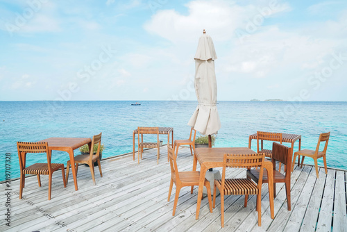 Foto auf AluDibond Licht blau Outdoor terrace with Empty wooden table and chair with Sea view of Indain ocean, Maldives background