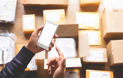 Obraz Online shopping concepts with youngman using smartphone on a lot of package box.Ecommerce market.Transportation logistic - fototapety do salonu