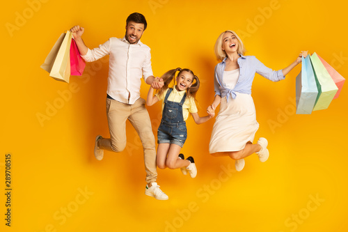 Valokuvatapetti Happy Family Jumping Holding Shopping Bags Over Yellow Background