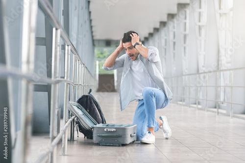 Desperate and shocked passenger checking his luggage at airport Canvas Print