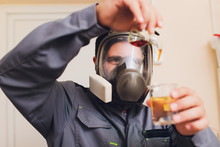 Technologist In White Protective Suit With Hairnet And Mask Working In Food And Beverage Factory. Man Specialist Checking Bottles For Beverage Production. The Use Of Iodine To Check The Readiness Of