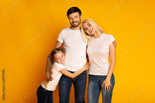 Valokuva  Loving Parents And Daughter Embracing Standing In Studio
