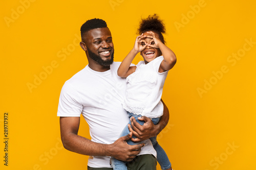 Stampa su Tela  Playful little afro girl making finger glasses, fooling on daddy's hands