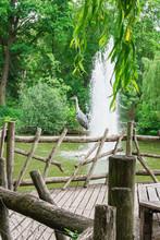 Water Fountain In The Park Volkspark Friedrichshain In Berlin, Heron Stands On A Wooden Railing