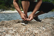 Athlete runner tying shoelaces before a morning jogging on the river, Kazakh jogger in nature close-up