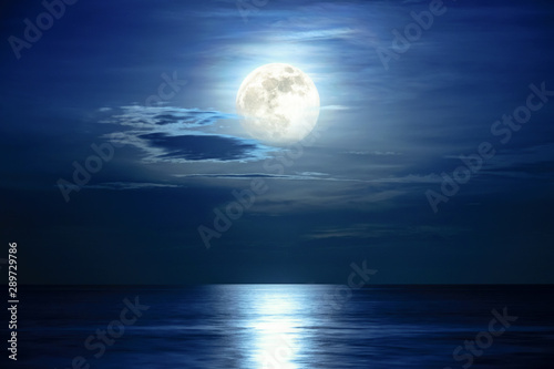 Photo sur Aluminium Bleu nuit Super full moon and cloud in the blue sky above the ocean horizon at midnight, moonlight reflect the water surface and wave, Beautiful nature landscape view at night scene of the sea for background