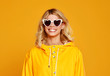 canvas print picture - happy emotional girl with sunglasses on autumn colored yellow background.