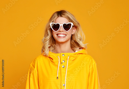Photo Stands Coffee bar happy emotional girl with sunglasses on autumn colored yellow background.