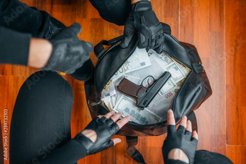 Fotografie, Tablou Two robbers in black uniform holds bag with money