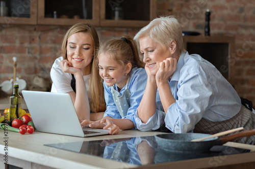 Happy female family looking for recipe on internet Fototapet